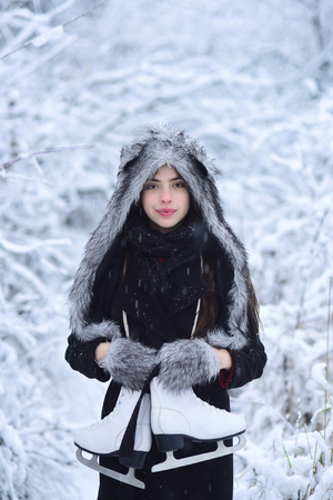 Sport, activity, health. Girl with pair of figure skates at trees in snow. Ice skating concept. Woman with skating shoes in winter clothes in snowy forest. Vacation, holidays, hobby, lifestyle.