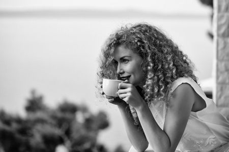 pretty woman with curly blond hair stands on balcony with coffee cup summer day on natural background Stock Photo