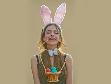 토끼 귀와 베이지 색 배경에 활 부활절 소녀. 부활절 전통과 상징. 이빨에 계란 바구니를 들고 여자입니다. 불임과 중생 개념. 봄 휴가 축하