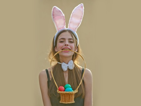 Easter girl with bunny ears and bow on beige background. Easter tradition and symbol. Woman holding wicker basket with eggs in teeth. Fertility and rebirth concept. Spring holiday celebration Imagens