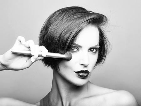 Girl with short dark hair red lips and make up with face brush applies blush on her cheeks in front of grey background Banco de Imagens