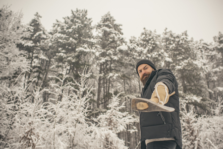 Bearded man with axe in snowy forest. Camping, traveling and winter rest. skincare and beard care in winter, beard warm in winter. Temperature, freezing, cold snap, snowfall. Man lumberjack with ax. Stock Photo