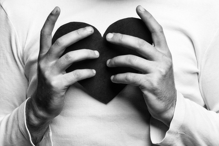 male hands of man in white shirt holding red paper heart closeup