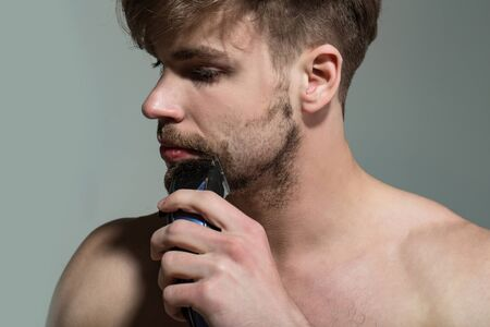 Beauty, skin care. Macho with electric shaver on grey background. Barber, hairdresser salon. Grooming, hygiene concept. Bearded man shave beard hair with trimmer.