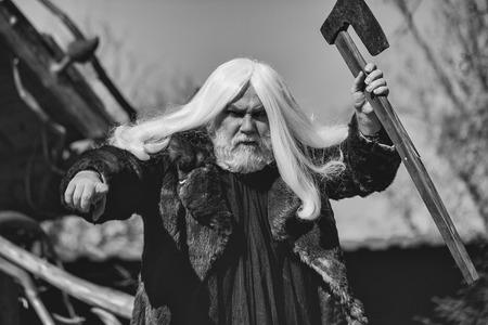 青空の背景に斧を持つ毛皮のコートで長い銀髪とあごひげを持つ残忍なドルイド老人