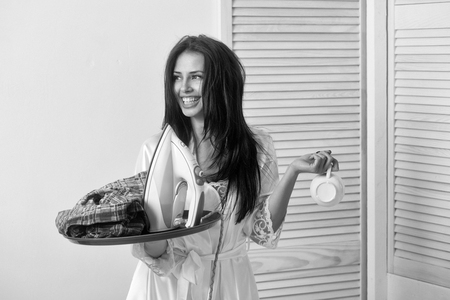 Happy pretty girl or beautiful woman, housewife, with long brunette hair in sexy dressing gown smiling with cup, electric iron and clothes for ironing on tray on white wall. Housework and housekeeping