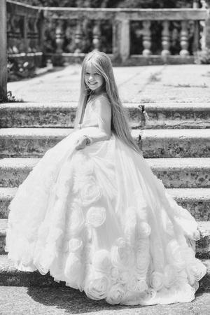 klein meisje jongen met lang blond haar en mooi lachend blij gezicht in prom prinses witte jurk staande zonnige dag buiten in de buurt van stenen trappen Stockfoto