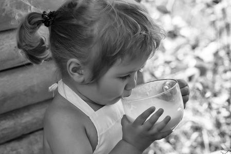 Schattige kleine jongen met blond haar paardenstaart in witte pinafore drinkt melk op zomerdag op houten achtergrond