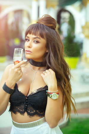 飲酒の概念。屋外でワインのグラスを持つ女性。カクテルパーティーや休日のお祝い。黒いレースのビスチェで長いブルネットの髪を持つ女の子。 写真素材