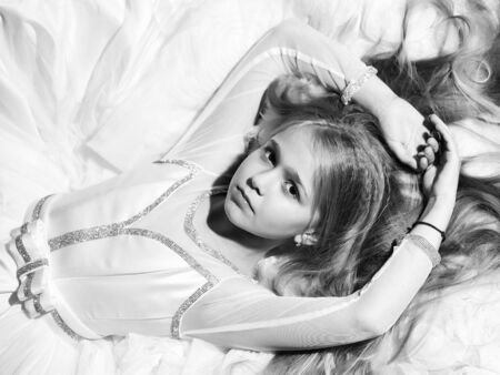 Small girl kid with long blonde hair and pretty serious face in prom dress lying on white fabric, closeup Stock Photo
