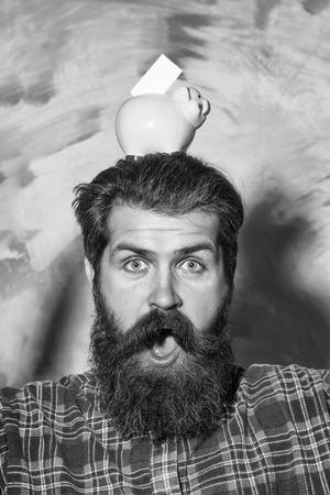 Verrast bebaarde man, blanke hipster, met lange baard en snor in rode plaid shirt met roze keramische spaarvarken en bankbiljet op hoofd op abstracte kleurrijke muur achtergrond. Geld besparen concept