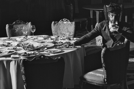 Handsome young man with beard and blond hair drinks wine from glass sitting at table with leftovers or residues food on dirty plates after banquet dinner in restaurant on dark background Reklamní fotografie