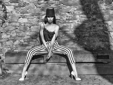 Young beautiful woman in stylish striped trausers and black hat outdoor sitting near stony wall Imagens