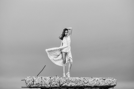 Pretty cute sexy blonde woman or girl stands with raised hand in blue dress waving on wind outdoor on broken concrete bunker on cloudy sky background
