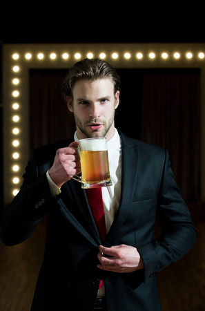 handsome man or businessman with beard and hairstyle in formal outfit with red tie hold beer glass near mirror with lamps, meeting and relax, bar and restaurant, sommelier, tasting and degustation