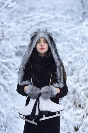 Ice skating concept. Woman with skating shoes in winter clothes in snowy forest. Sport, activity, health. Vacation, holidays, hobby, lifestyle. Girl with pair of figure skates at trees in snow.