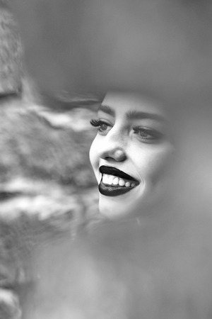 Smiling girl with beautiful face and red lips near stony wall with blurred frame Stock Photo