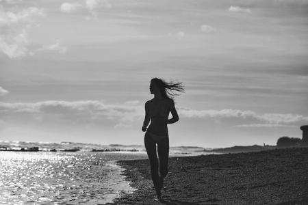 かわいい女の子や美しい女性、セクシーなスリムなブルネット、海や海の海岸に沿って砂浜で走る黄色の水着で、太陽の光に輝く水面、牧歌的なバ