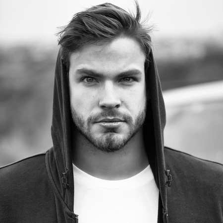 Young man with bearded serious face brown hair and blue eyes in casual dark hood on head and white t shirt outdoor 免版税图像