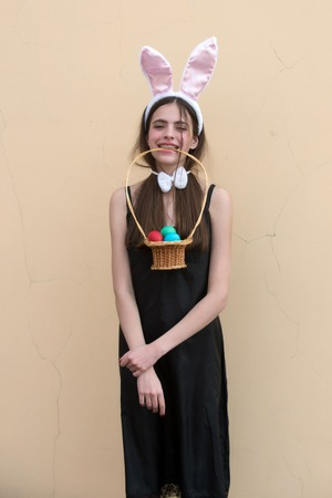 Easter woman holding wicker basket with eggs in teeth. Girl with rosy bunny ears and bow on beige background. Fertility and rebirth concept. Easter tradition and symbol. Spring and holiday celebration
