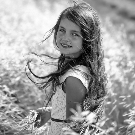 Portrait of pretty young brunette smiling girl with long hair in white lace dress looking forward standing in valley among yellow spikelet sunny windy day outdoor, square photo Banco de Imagens
