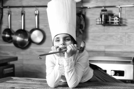 Small girl with ladle in cook hat. Cooking, food, study