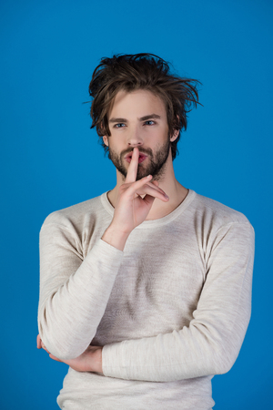 Barber and hairdresser, male fashion. Sleepy man with beard on blue background. Man with disheveled hair in underwear. Morning wake up, everyday life. Insomnia, energy, single with uncombed hair. Stock Photo