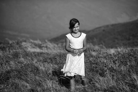Giovane bella ragazza bruna sorridente in abito estivo di pizzo bianco in piedi in valle di montagna con erba spikelet profonda secca in primavera giornata di sole all'aperto su sfondo blu naturale, immagine orizzontale Archivio Fotografico - 93535393