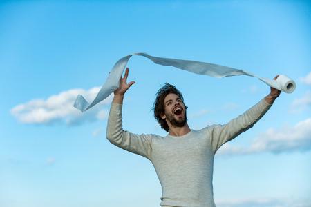 Homme au visage heureux tenir le papier toilette, célibataire. Homme en sous-vêtements aux cheveux ébouriffés, matin Stérilité et pureté. Hygiène et sanitaire. WC et toilettes. la diarrhée