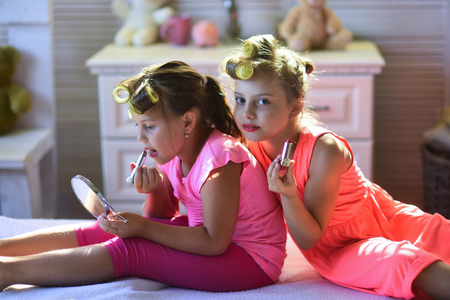 Little girls do makeup sitting in room. Stock Photo