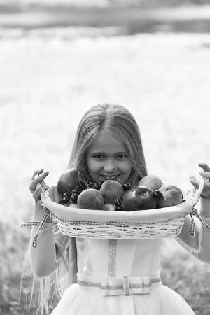 klein meisje kind met lang blond haar en mooi lachend blij gezicht in prom prinses witte jurk staande zonnige dag buiten in de buurt van water met fruitmand met rode appels perzik en kers
