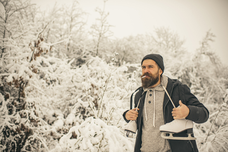 Man in thermal jacket, beard warm in winter. skincare and beard care in winter. Winter sport, Christmas. Temperature, freezing, cold snap. Bearded man smoking cigarette with skates in snowy forest.