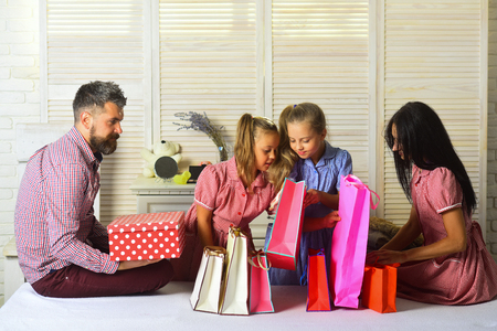 Family shopping and celebration concept. Man, woman and adorable kids with gifts at home. Family with cheerful faces open presents at home. Mother, father and daughters with shopping bags and packs. 版權商用圖片