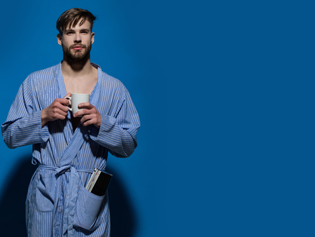 Morning routine concept. Man with cup on blue background. Breakfast, coffee or tea time. Bachelor in dressing gown with mug. Hot drink, diet, health, copy space