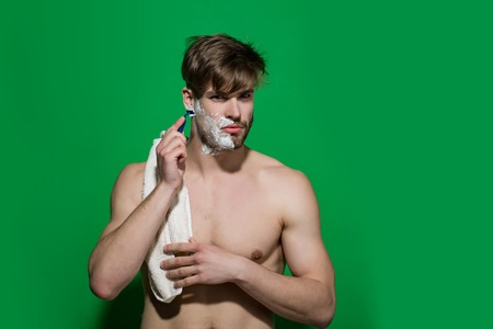 Morning routine concept. Man shave bearded face on green background. Bachelor with shaving cream, razor, towel on sexy torso. Beauty, grooming, hygiene. Skincare, health, wellness, copy space