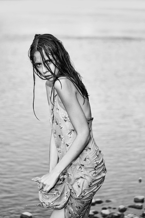 Pretty girl cute beautiful woman in wet sexy dress wrings water from clothes on river background