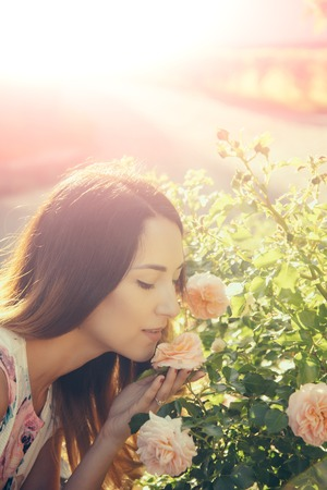 Woman or girl smelling blossoming rose flower scent on sunny day in summer garden. Beauty of nature concept