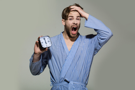 Man yawn with alarm clock on grey background. Macho with sleepy face in dressing gown. Morning, wake up concept. Time, routine, deadline.