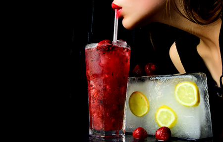 Party and summer vacation. Bar and restaurant, lemonade. Cocktail with strawberry for young girl isolated on black. Thirst and refresh. woman drink cocktail with ice cube, copy space