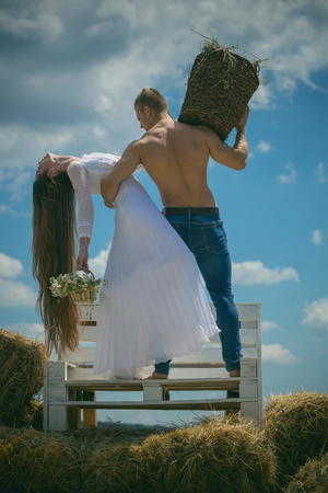 Couple in love hug on bench on blue sky. Woman with long hair in white dress with flowers. Romance, relationship, relations. Summer vacation concept. Man with muscular torso hold wicker basket.