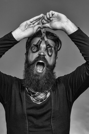 young handsome bearded man with long beard moustache and brunette hair holding hairdresser or barber scissors with emotional face in studio on grey background Reklamní fotografie