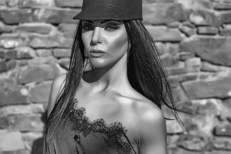 Young beautiful woman in stylish black hat outdoor near stony wall closeup Imagens