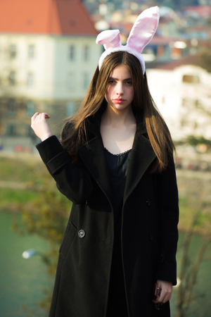 Easter girl wearing bunny ears and black coat on natural background. Spring and Easter. Holiday celebration concept