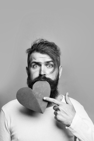 young bearded man with romantic face holding red paper heart in studio on grey background, copy space