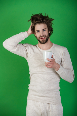 Insomnia, refreshment and energy. Cold and flu, single. Man with disheveled hair drink mulled wine. Morning with coffee or milk. Happy guy with tea cup on green background. Stock Photo