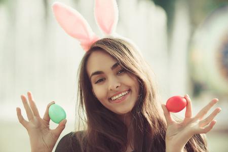 소녀 또는 장미 빛 토끼 귀와 컬러 계란, 녹색 및 빨강, 함께 포즈를 취하는 긴, 갈색 머리 머리 여자가 귀여운 여자가 흐린 자연 배경에 화창한 날에 손