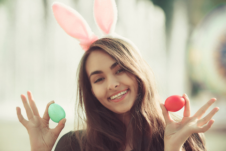 girl or cute woman with rosy bunny ears and long, brunette hair posing with colored eggs, green and red, in hands on sunny day on blurred natural background. Easter. Spring 版權商用圖片