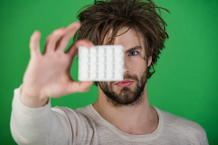 Drug and antidepressant, insomnia. Man with pills in blister pack. Health and medicine, hangover. Dieting pill and vitamin, man with anabolic. Cold, flu and headache treatment, hypnotic tablet. Stock Photo