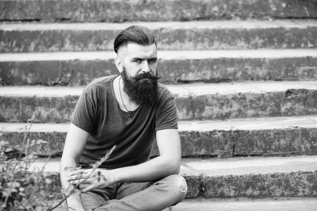 Handsome young stylish hipster man with long beard in grey shirt sitting outdoor on stony stairs with green plant