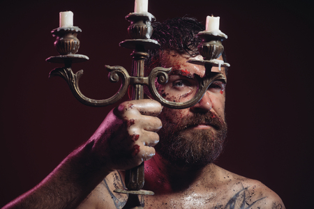 Halloween holidays celebration. Hipster hold candlestick with candles on purple background. Bearded man with bloody face, tattooed chest with candleholder.